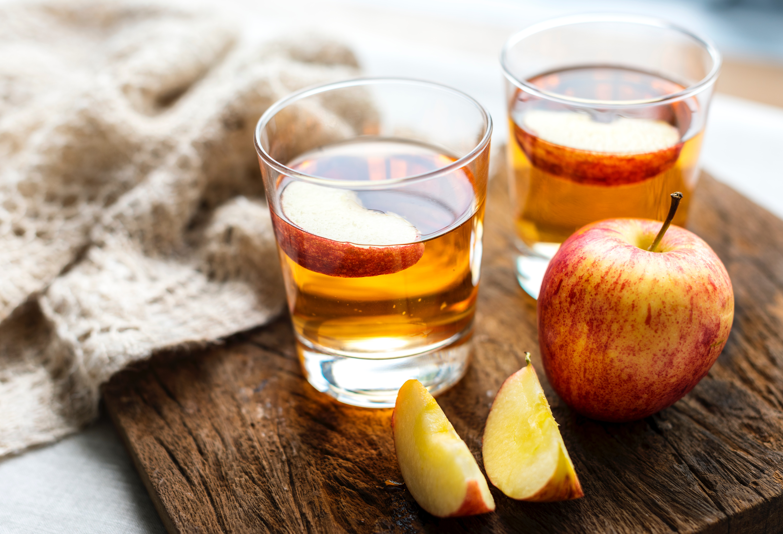 Zwei Gläser Cidre mit Äpfeln davor
